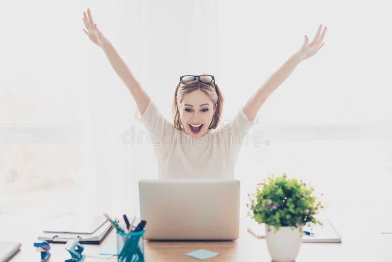 Gelukkige opgewekte succesvolle onderneemster die met laptop zitting bij de zitting van de werkstationwerkplaats bij lijst in lic royalty-vrije stock fotografie