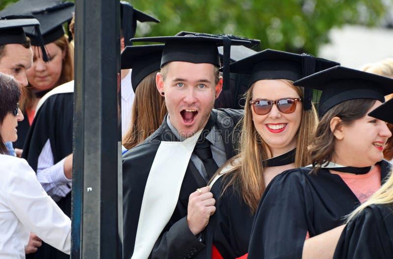Gelukkige opgewekte universitaire studenten die graduatiedag een diploma behalen stock afbeelding