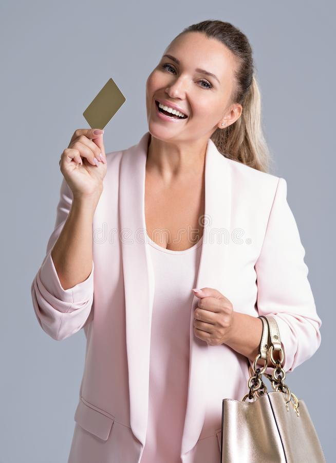 Gelukkige opgewekte verraste jonge geïsoleerde vrouw met creditcard stock afbeeldingen