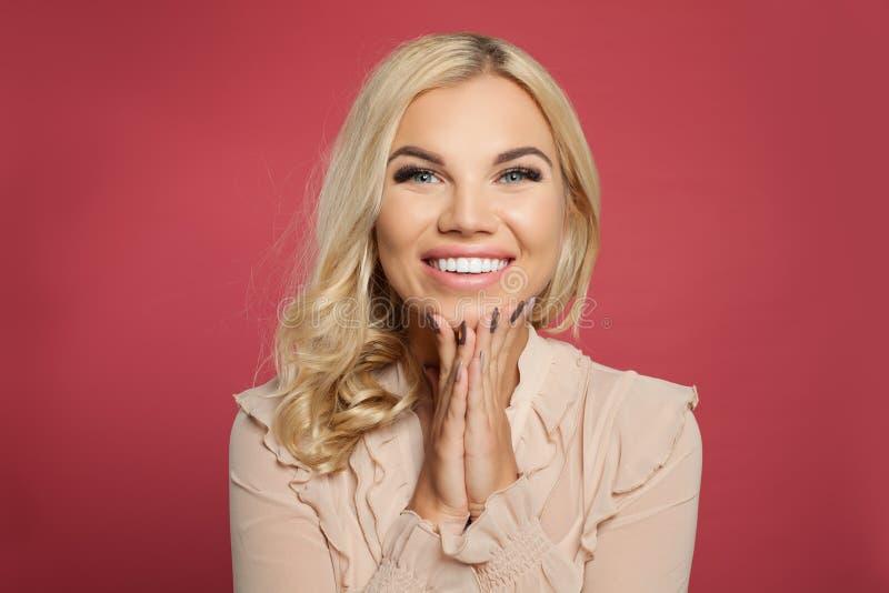 Gelukkige opgewekte vrouw die tegen kleurrijke roze muurachtergrond glimlachen Het vrij krullende portret van het haarmeisje Posi royalty-vrije stock afbeeldingen