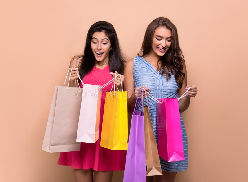 Gelukkige opgewekte vrouwen die het winkelen zakken onderzoeken royalty-vrije stock foto's