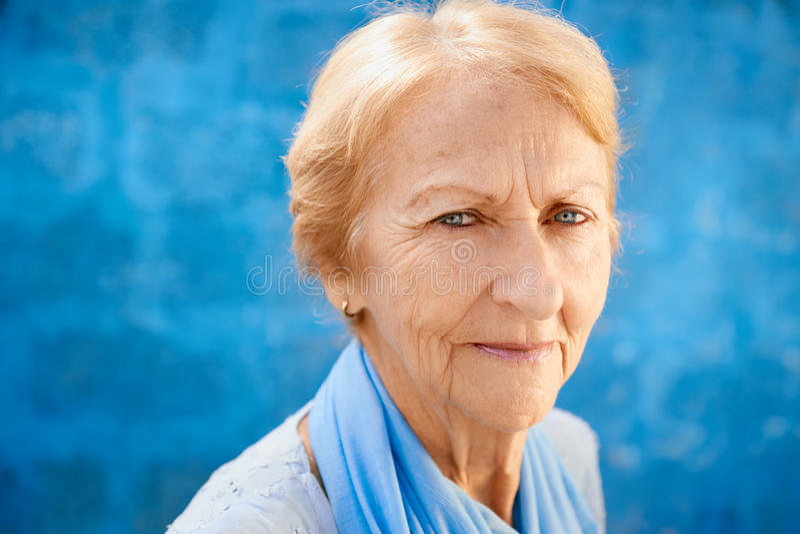 Gelukkige oude blonde vrouw die en camera glimlachen bekijken royalty-vrije stock fotografie