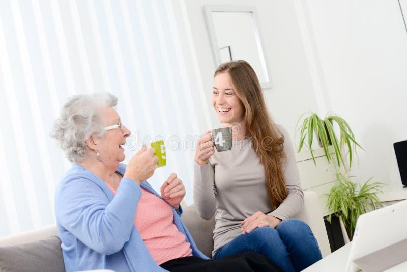 Gelukkige oude hogere vrouw het besteden tijd en het drinken thee met een vrolijk jong meisje thuis royalty-vrije stock afbeelding