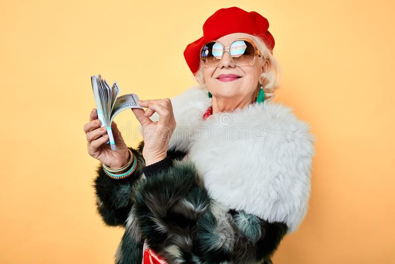 Gelukkige oude modieuze vrouw in zonnebril die haar geld opscheppen stock afbeelding