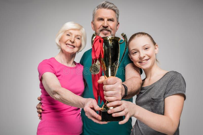 Gelukkige oude paar en meisjes de trofee en de medailles van de holdingssport royalty-vrije stock afbeelding