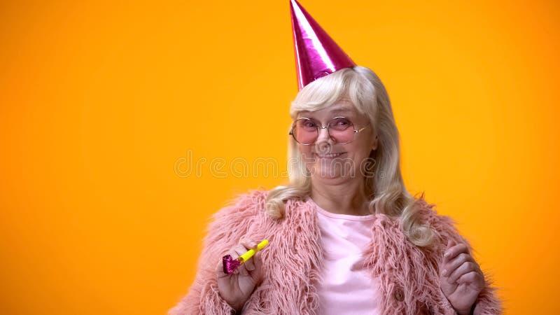 Gelukkige oude vrouw die in roze laag en ronde glazen verjaardagsverjaardag vieren royalty-vrije stock afbeelding
