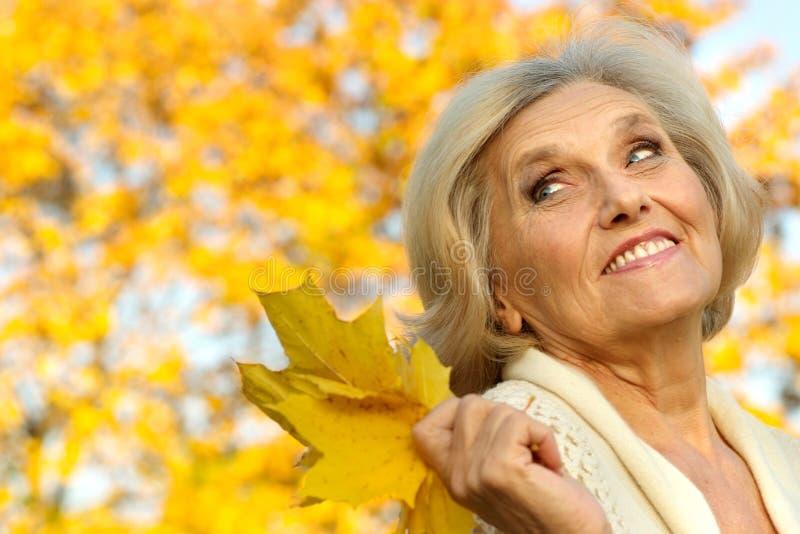 Gelukkige oude vrouw op een geel stock afbeelding