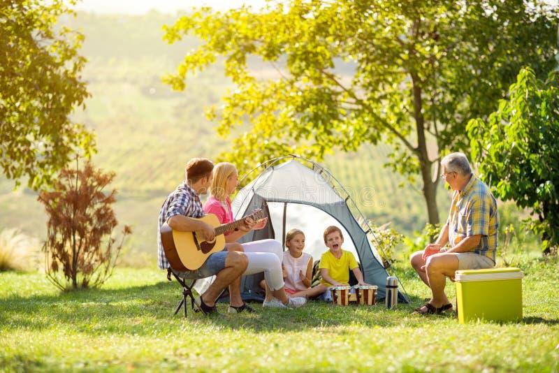 Gelukkige ouder en kinderen die van het kamperen genieten stock afbeelding