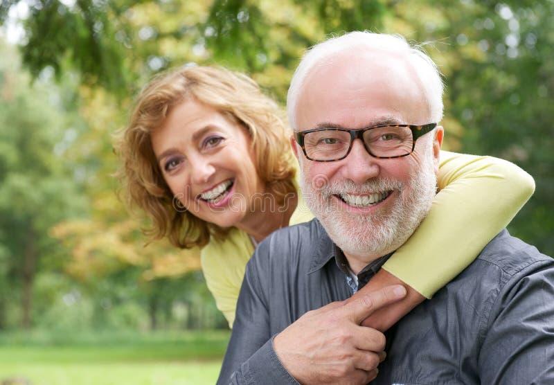 Gelukkige oudere vrouw die de glimlachende oudere mens omhelzen stock afbeeldingen