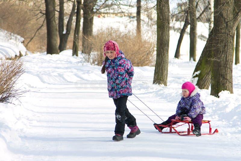 Gelukkige oudere zuster die haar jonge zuster op de sleeën in sneeuw de winterpark trekken royalty-vrije stock foto