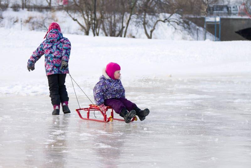 Gelukkige oudere zuster die haar jonge zuster op een slee op het ijs in sneeuw de winterpark trekken royalty-vrije stock foto's