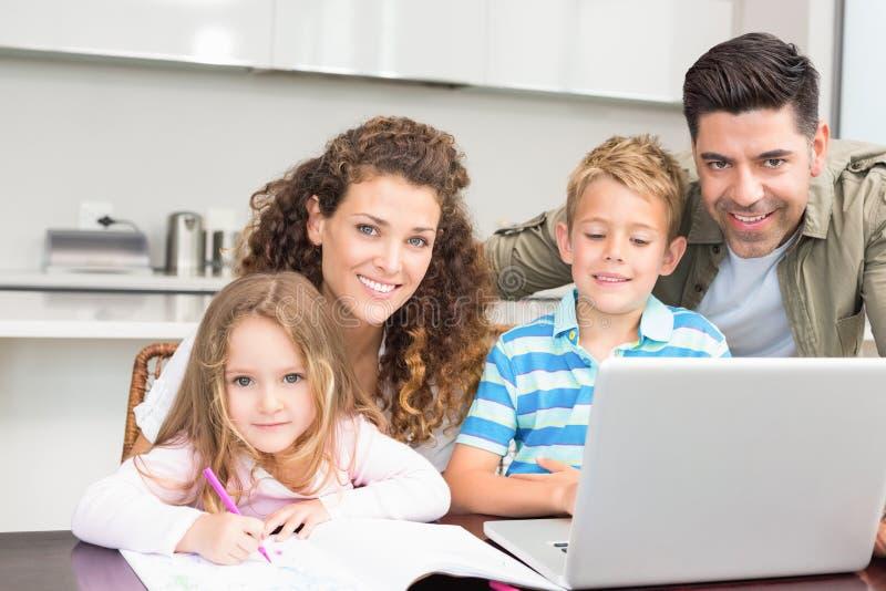Gelukkige ouders die en laptop met hun kinderen kleuren met behulp van royalty-vrije stock foto