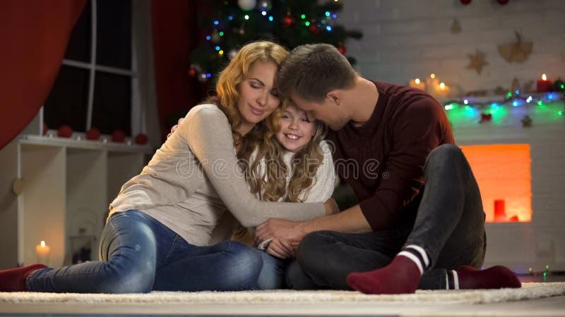 Gelukkige ouders die houdende van dochter, familie het vieren Kerstmis samen omhelzen royalty-vrije stock afbeelding