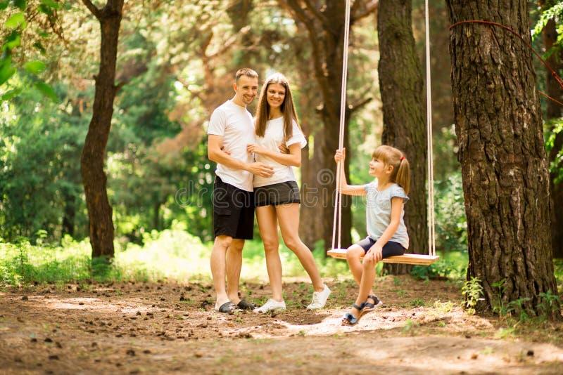 Gelukkige ouders die kindmeisje slingeren bij park royalty-vrije stock fotografie
