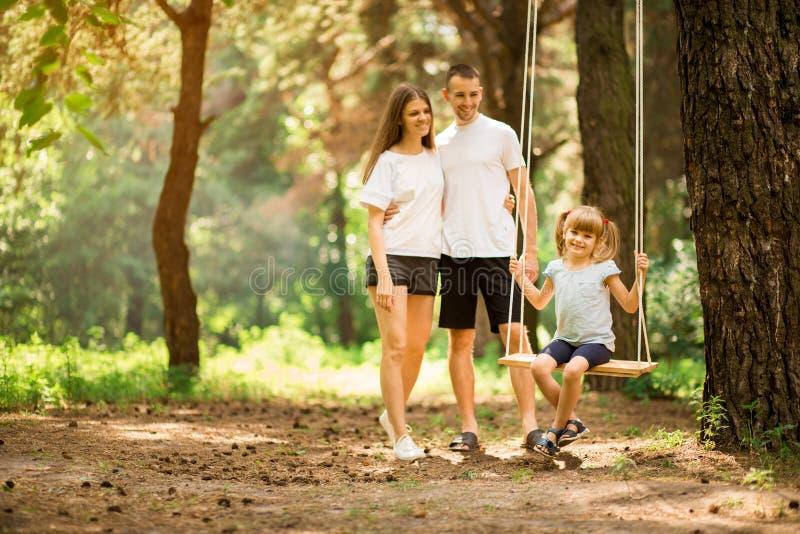 Gelukkige ouders die kindmeisje slingeren bij park royalty-vrije stock foto