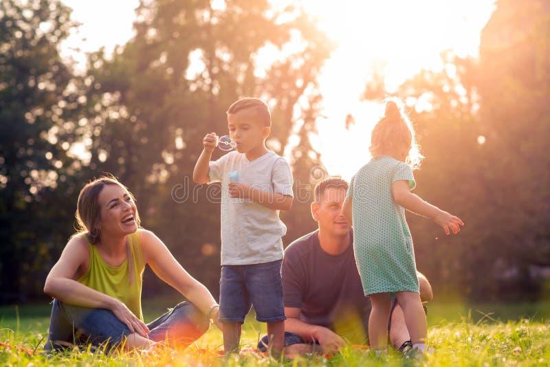 Gelukkige ouders die met buiten kinderen spelen stock fotografie