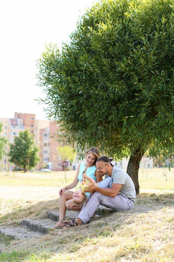 Gelukkige ouders die met dochter spelen openlucht stock foto's