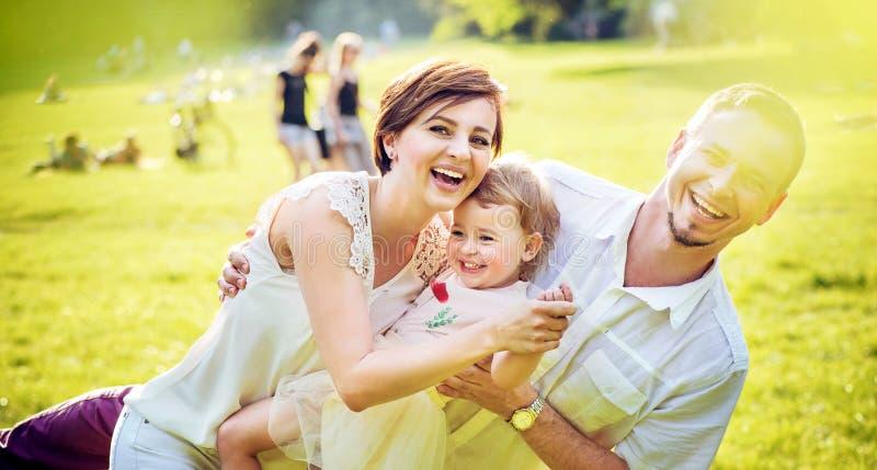 Gelukkige ouders die met hun dochter spelen stock afbeeldingen