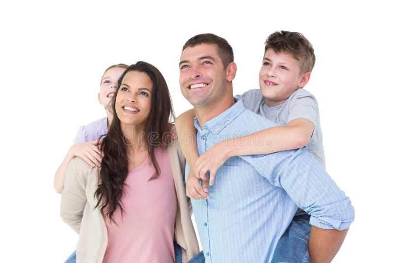 Gelukkige ouders die op de rug rit geven aan kinderen terwijl omhoog het kijken royalty-vrije stock afbeeldingen
