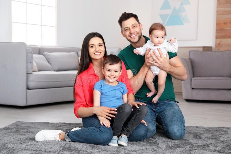 Gelukkige ouders en hun leuke kinderen die op vloer thuis zitten stock fotografie