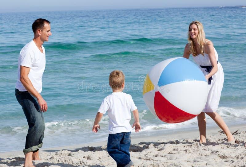 Gelukkige ouders en hun zoon die met een bal spelen royalty-vrije stock afbeelding