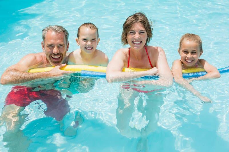 Gelukkige ouders en jonge geitjes in pool stock foto