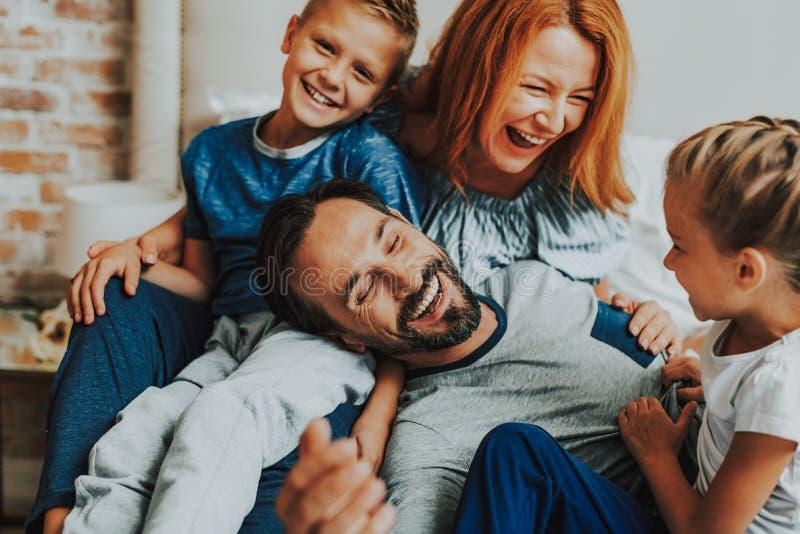 Gelukkige ouders en twee jonge geitjes die samen lachen stock afbeeldingen