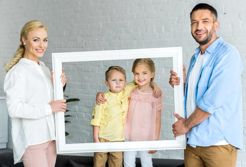 gelukkige ouders kader houden en leuke kleine kinderen die stock foto's