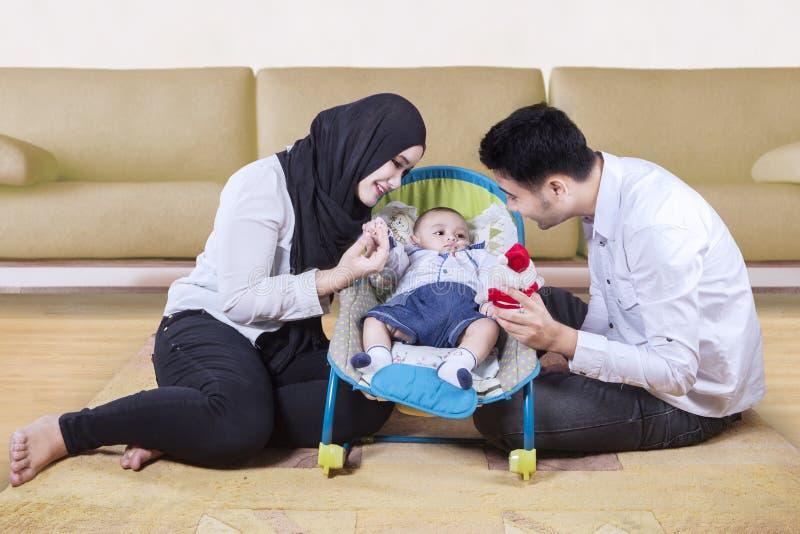 Gelukkige ouders met baby in de wandelwagen stock afbeeldingen