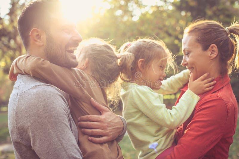 Gelukkige ouders met dochters, die aandeelliefde koesteren stock fotografie