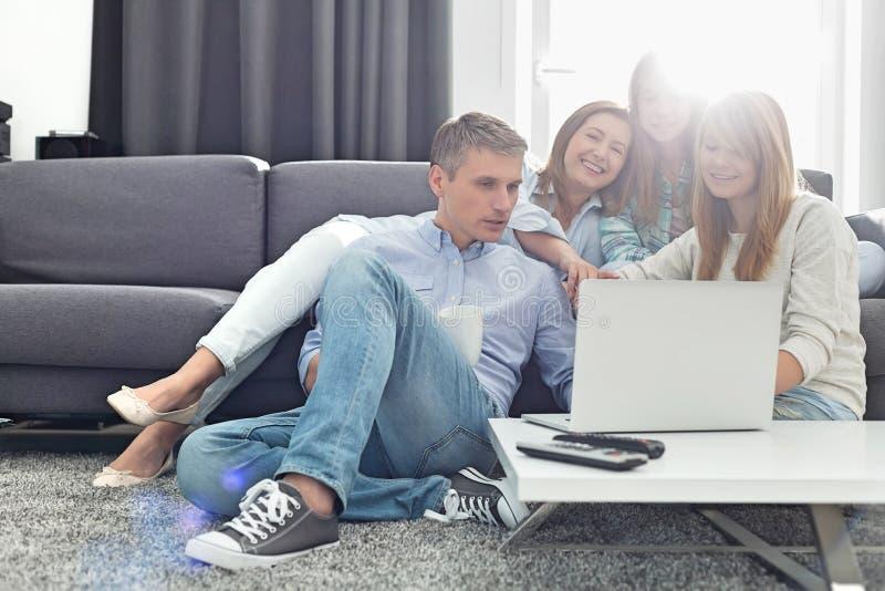 Gelukkige ouders met dochters die laptop in woonkamer met behulp van stock foto's