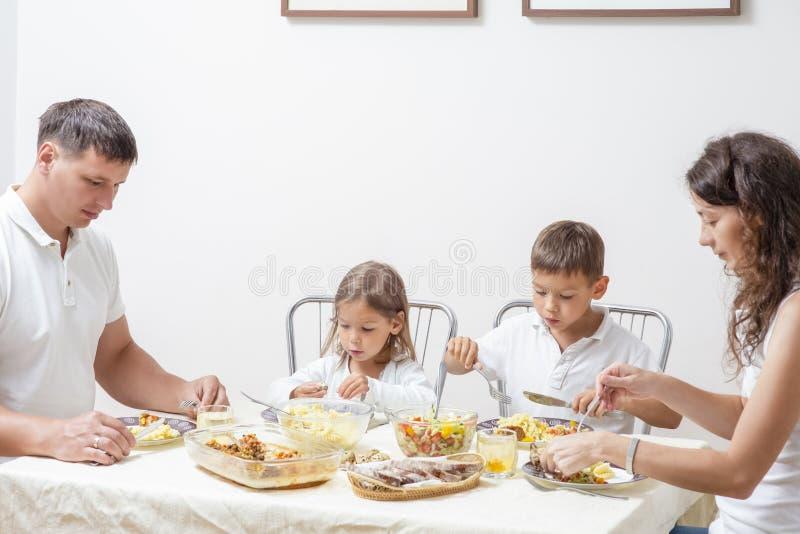 Gelukkige Ouders met Hun Kinderen die Ontbijt hebben thuis stock afbeeldingen
