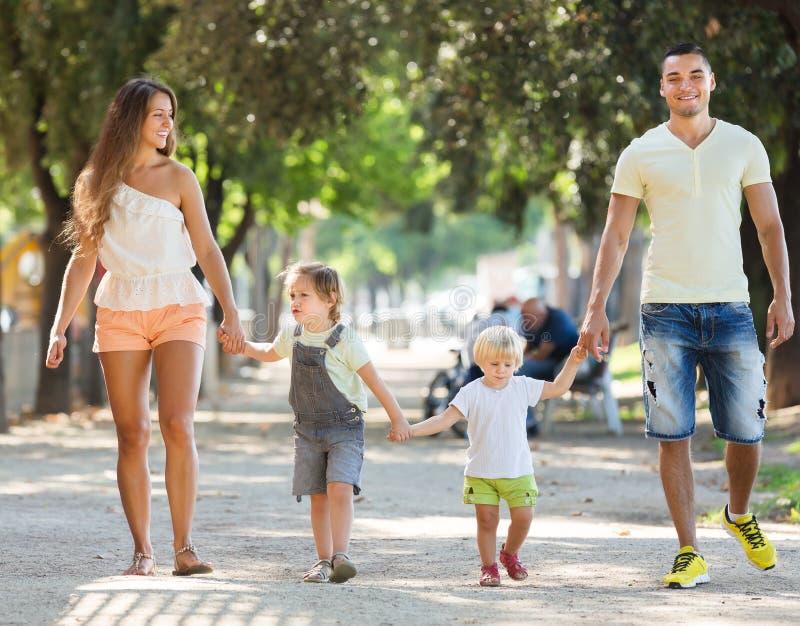 Gelukkige ouders met kleine kinderen in park royalty-vrije stock afbeeldingen