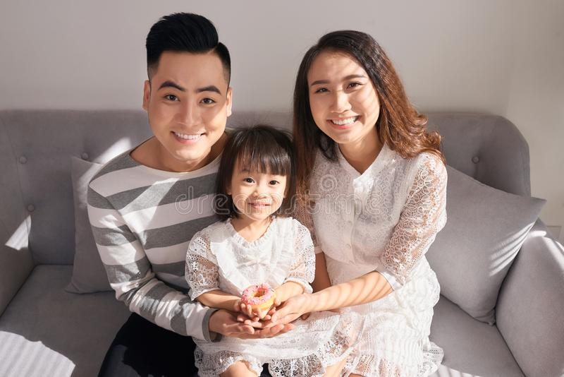 Gelukkige ouders met leuk weinig dochterzitting op laag en KMIO stock fotografie
