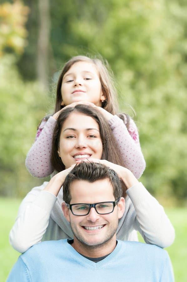 Gelukkige ouders met mooie dochter in park. stock fotografie