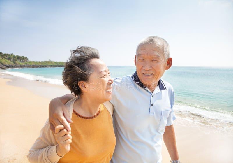 Gelukkige oudsten die op het strand lopen stock foto's