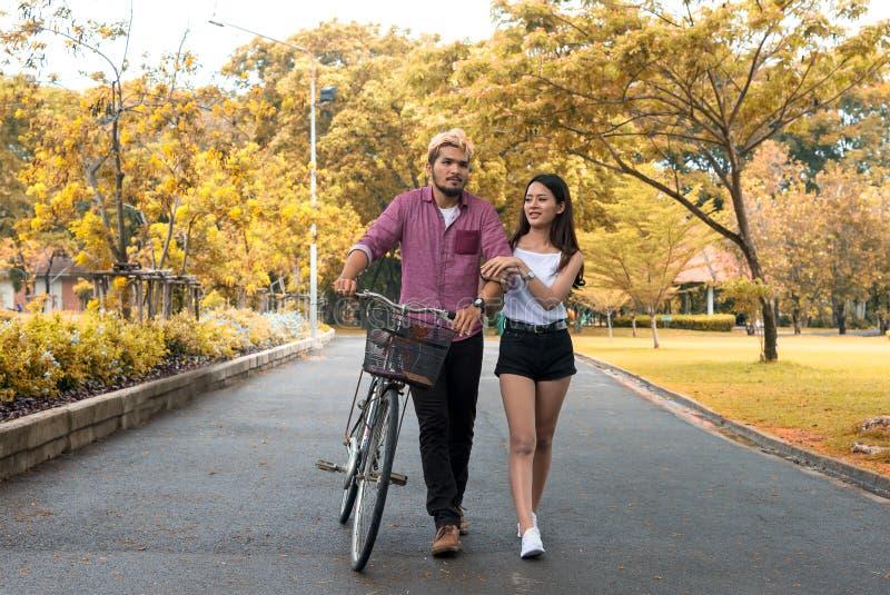 Gelukkige paar berijdende fiets in het park, stock afbeelding
