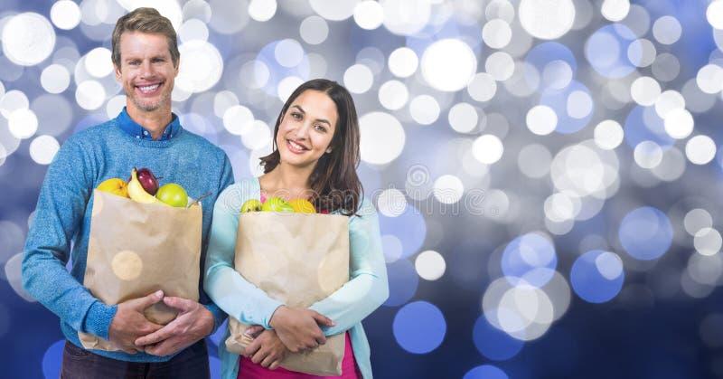 Gelukkige paar dragende vruchten in document zak over bokeh royalty-vrije stock afbeeldingen