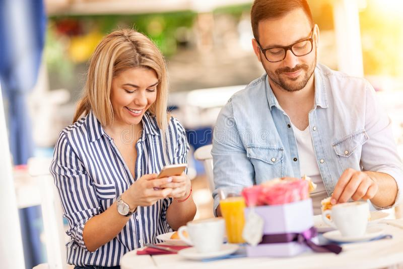 Gelukkige paar het besteden ontbijttijd samen in restaurant stock afbeeldingen