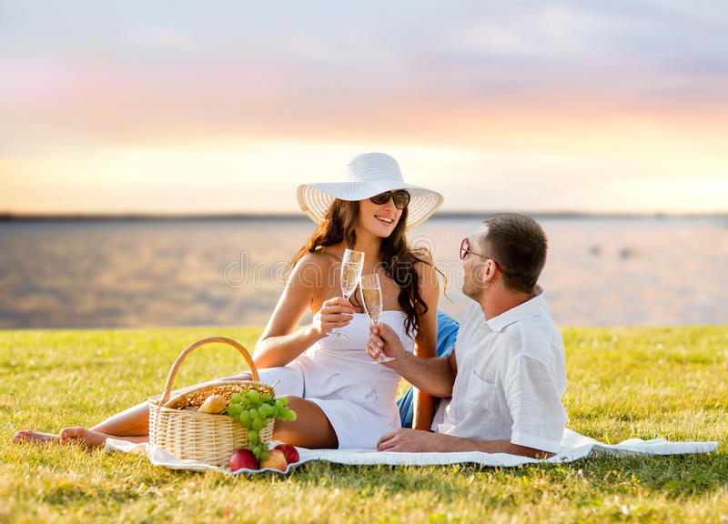 Gelukkige paar het drinken champagne op picknick stock afbeelding
