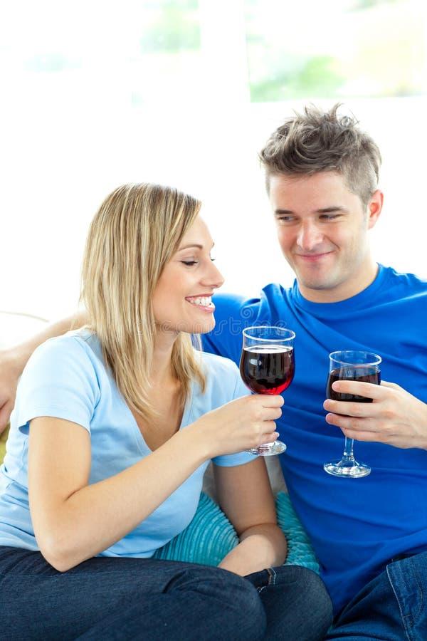 Gelukkige paar het drinken wijn samen in woonkamer stock afbeelding