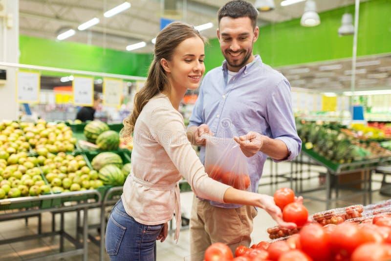 Gelukkige paar het kopen tomaten bij kruidenierswinkelopslag stock foto's