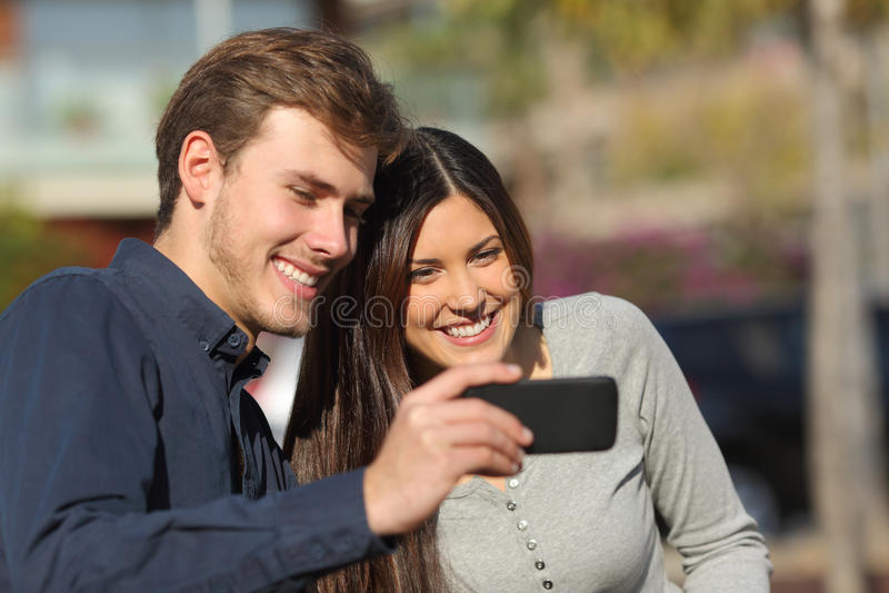 Gelukkige paar het letten op media in een slimme telefoon in openlucht royalty-vrije stock foto