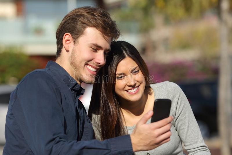Gelukkige paar het raadplegen telefooninhoud in een park stock afbeelding
