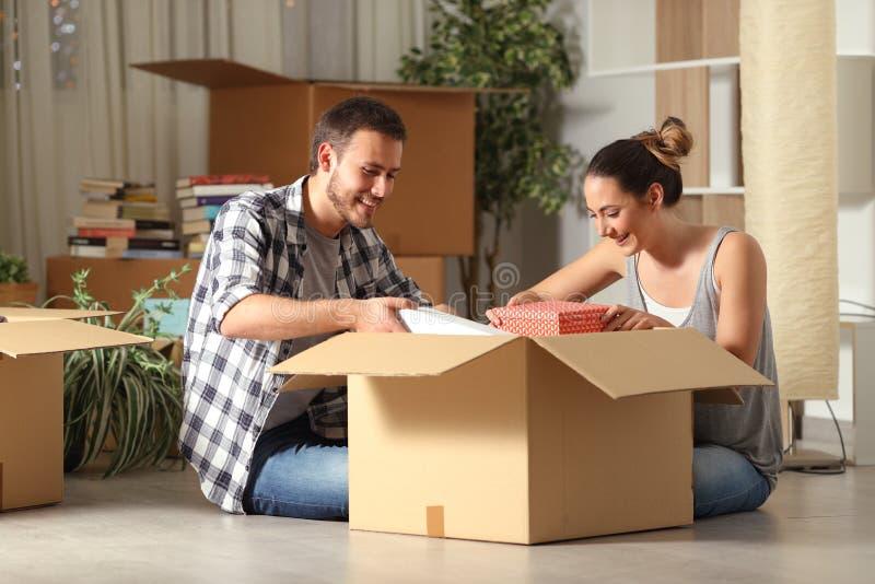 Gelukkige paar unboxing bezittingen die huis op de vloer bewegen royalty-vrije stock afbeelding
