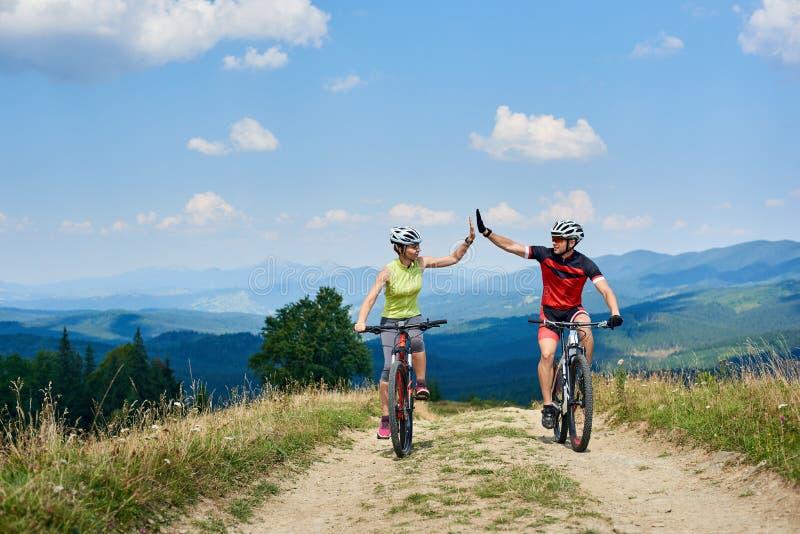 Gelukkige paarfietsers in professionele sportkleding en helmen die de dwarsfietsen van het land berijden stock afbeeldingen