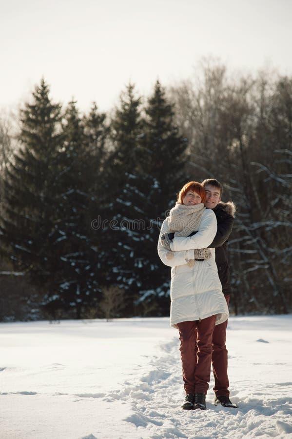 Gelukkige paaromhelzing in de winterpark op achtergrond van bos royalty-vrije stock afbeeldingen