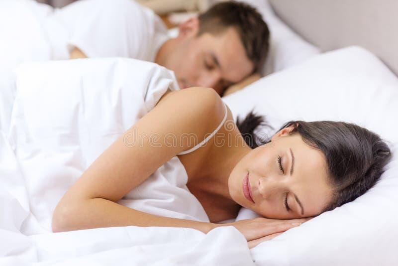 Gelukkige paarslaap in bed stock foto's