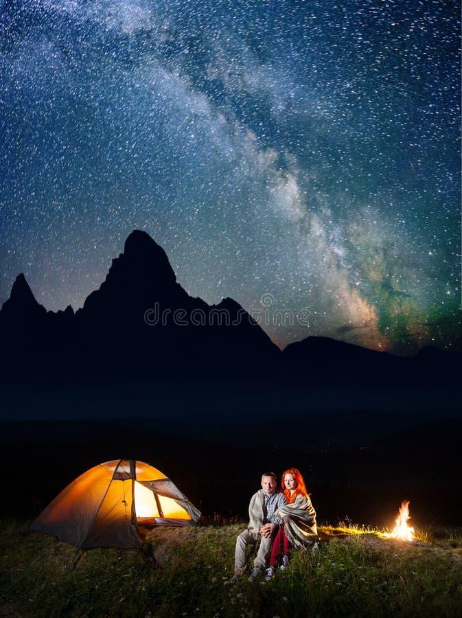 Gelukkige paarwandelaars samen omvat met een plaidzitting onder sterrige hemel dichtbij kampvuur en kamp bij nacht royalty-vrije stock afbeelding