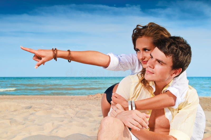 Gelukkige paarzitting op het strand stock afbeelding